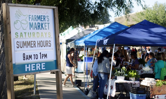 Farmer's Market sign, with vendor booths in background.