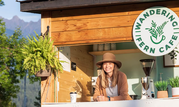 A woman is standing inside her pop-up cafe, with a fern hanging at the front.