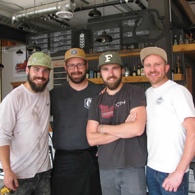 Four smiling, bearded young men: Ian McCann, Doug Wagner, Jesse Roberts and Fred Williams, are the team that oversees operations at Fire Hall Kitchen & Tap