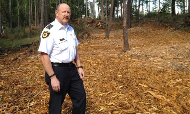 Kimberley Fire Chief Al Collinson is standing on tree chips from a fuel reduction project at Duck Pond.