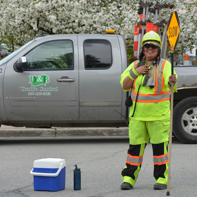 Female flag person, Theresa Clarke, in high-visibility gear, with a D&B Flagging truck behind her