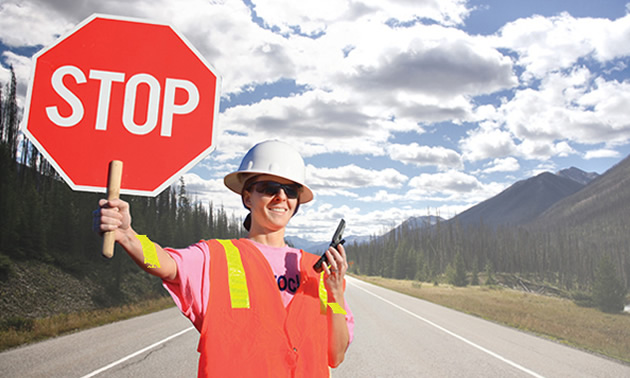 Flagger holding up stop sign.