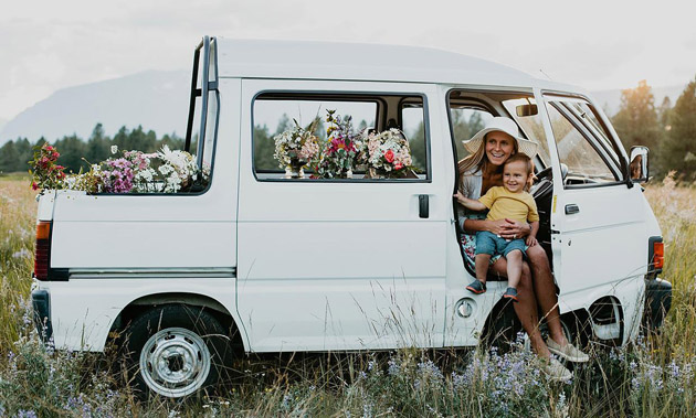 Owner of Flora Bora Blooms and son posed in flower delivery truck.