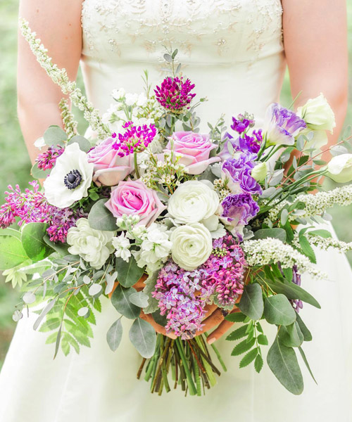 Close-up of purple and white bridal bouquet.