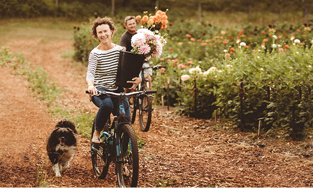 Owners of Stone Meadows Gardens riding bikes and carrying flowers.