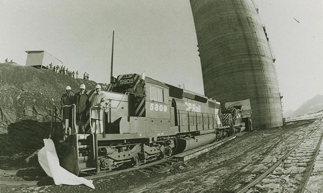 An old black and white photo of three men on a CPR train engine in front of a tall silo