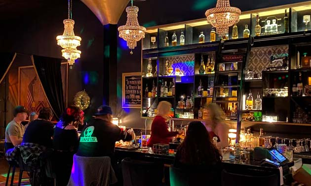 Interior of Frisky Whisky Tapas Lounge, showing bar area and three art-deco style lights above bar.