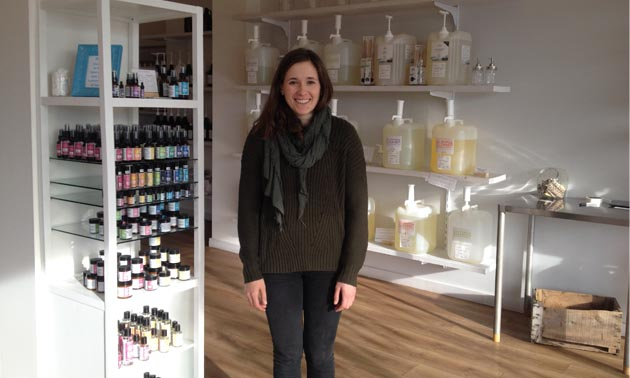 Jill Bentley-Lobban is standing in her store with bulk personal care products behind her.