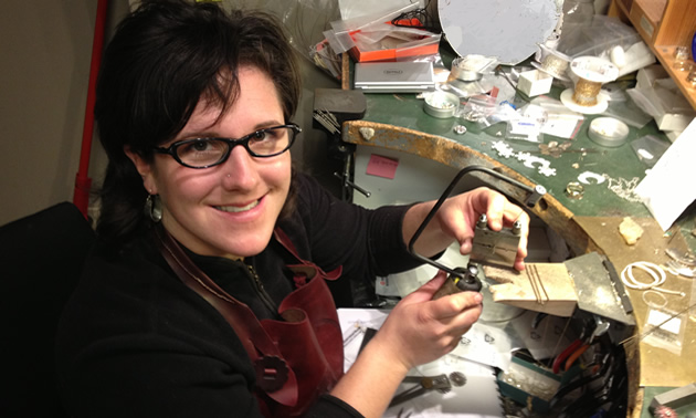 Arleigh has short brown hair and glasses, she sits at a curved and cluttered work dest, holding some of the tools of the trade.