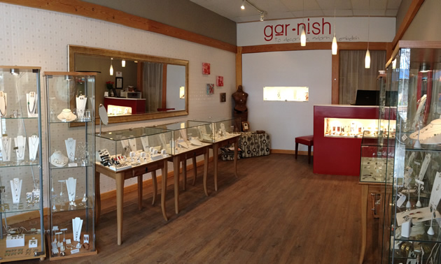 An airy and open showroom has jewelry showcases, wood floors and red accents.