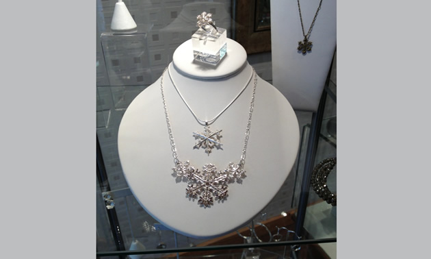 A selection of snowflake design necklaces are showcased on a mannequin.