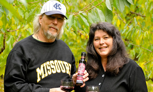 Casually dressed man and woman hold a small bottle and two wine glasses holding a dark red liquid.
