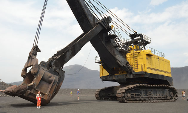 A man and child are dwarfed by the giant mining machine that is parked beside them.
