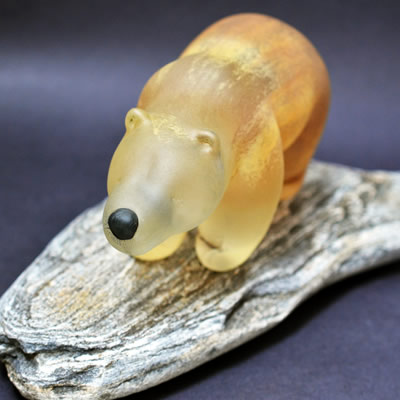 An ivory-coloured glass bear is standing on a piece of wood.
