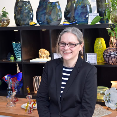 Diana Fox is standing in front of display shelves of glass items.