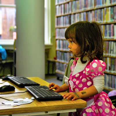 Little girl dressed in pink using a computer.