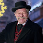 Broadly smiling man wearing  a black bowler hat and topcoat gestures with his right hand toward the festive lights on the street behind him