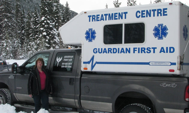 A woman standing beside a black pickup truck carrying a white camper with a sign saying Treatment Centre Guardian First Aid