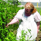 Rachel Beck, wearing a white dress, reaches out to a large herbal plant.