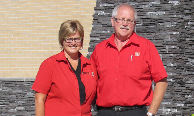 Walter and Heather Ingram, wearing their red Home Hardware shirts, stand in front of their new building.