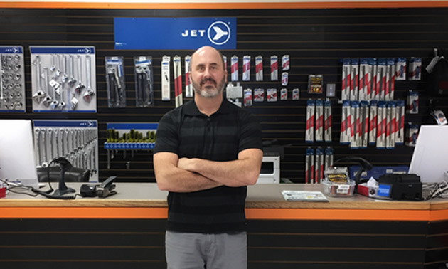 Mike Konkin, one of the owners of Trail Hammer and Bolt, is standing in front of the store counter with goods for sale in the back.