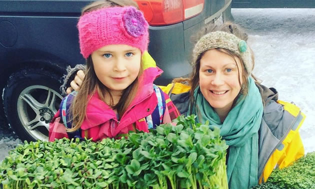 Mother and daughter are carrying trays of greens for the farmers market.
