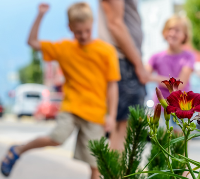 Flowers in the foreground, children and dad in soft-focus background