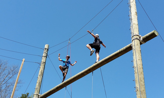 Two people on a high-ropes course.