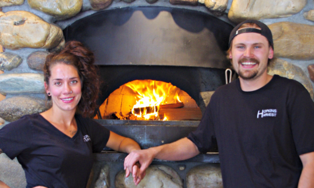 Kerstan Hopkins and boyfriend Matthew Larsen, co-operators and managers of Hopkins Harvest, pose next to the gourmet wood-fired pizza oven.