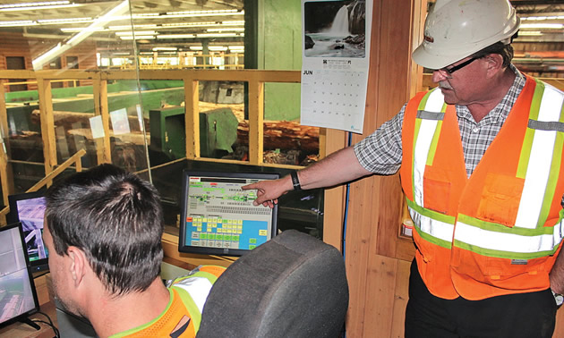 Worker pointing at computer.