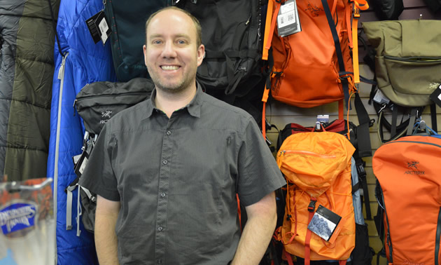 Smiling man standing in front of a wall display of backpacks