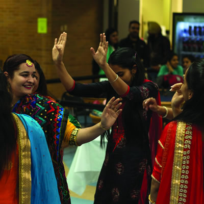 East Indian girls, dressed in colourful embroidered saris, dancing with hands in the air.