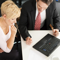 A financial planner looks over finances on a laptop with a couple.
