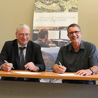 Selkirk College President Angus Graeme (right) and International Academic Pathways Officer Cyril Gavaghan of the Institute of Technology Tralee sign a Memorandum of Understanding.