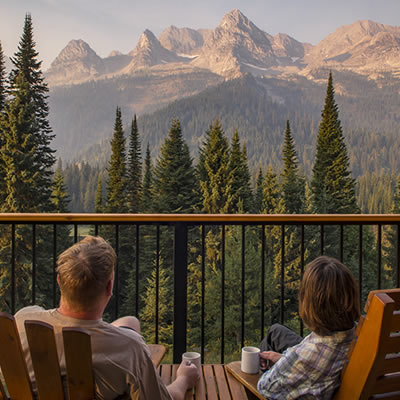 Two people relaxing, looking at a view of mountains.