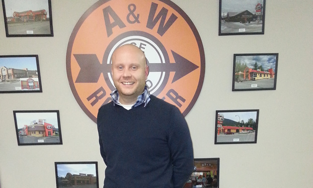 Close-up of a young, bald man in front of an A&W root beer sign.
