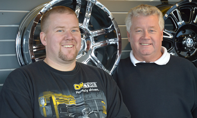 Two smiling men, one younger and one older, stand in front of a display of shiny wheel rims