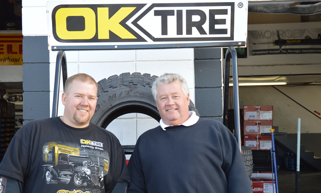 Two men, one younger and one older, stand under an OK Tire sign