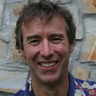 Head-shot of smiling, outdoorsy-looking middle-aged man wearing a flower-patterned shirt