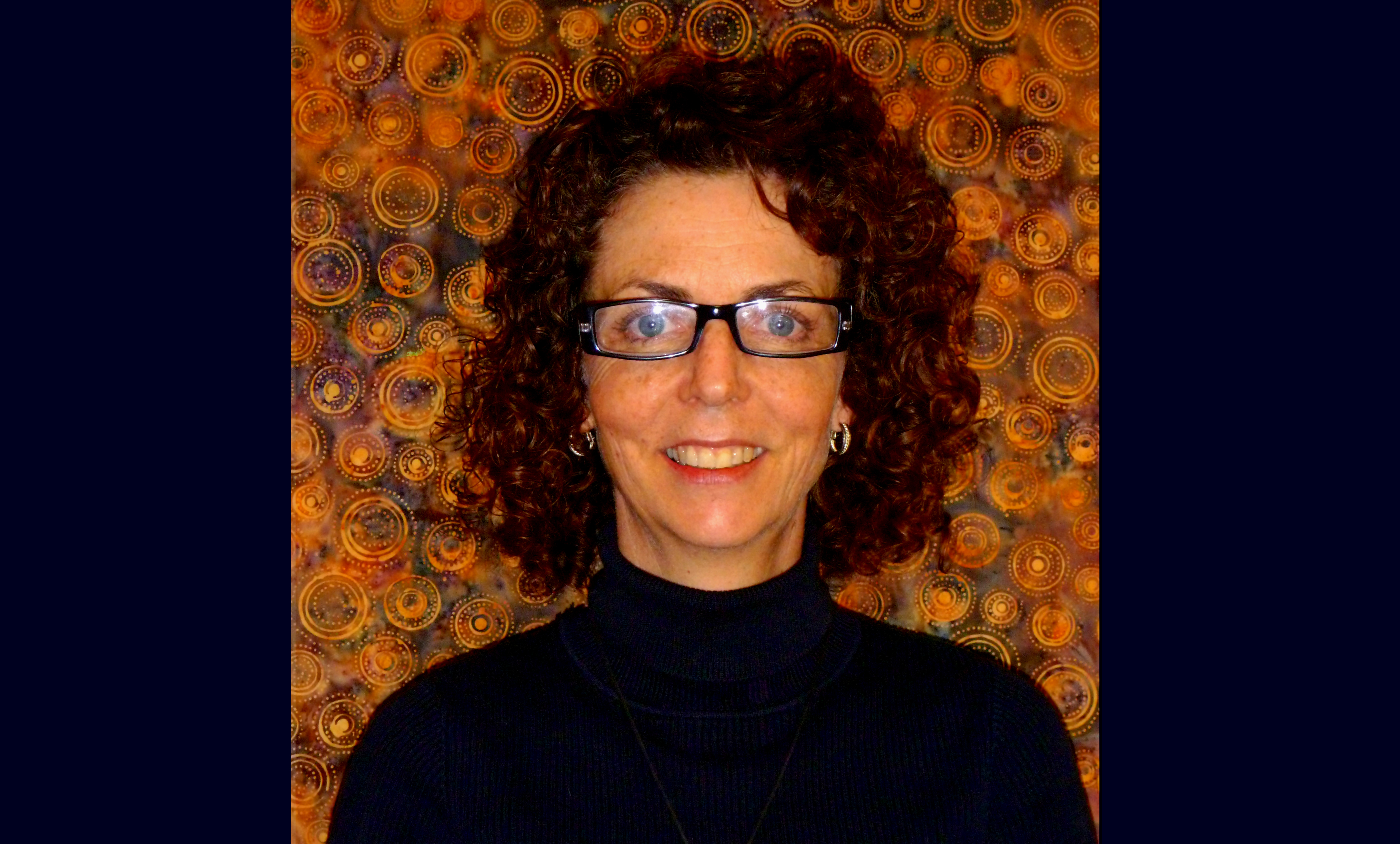 Joanne smiles at the camera in front of a gold-swirly pattern. She wears glasses and a dark blue shirt and has curly dark brown hair.