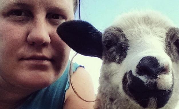 A close up photo of Jo Ferris and a lamb.