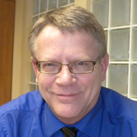 John Malcolm has glasses, a sky-blue shirt and a tie.