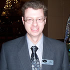 Man in business suit, wearing a Prestige Resorts name tag, stands beside a Christmas tree.