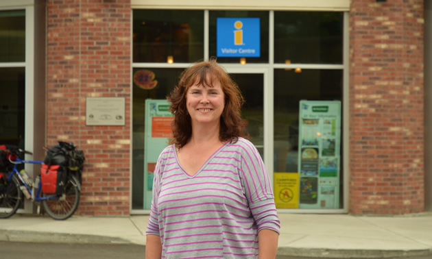 Judy Goodman, executive director of Revelstoke Chamber of Commerce in Revelstoke, B.C., stands in front of the visitor centre and chamber of commerce building.