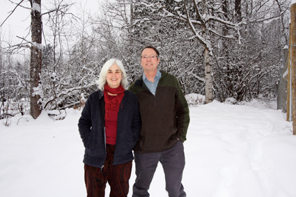 A man and woman stand in a snowy landscape