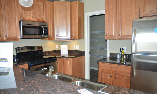Compact kitchen has granite counters, stainless steel appliances and a walk-in pantry