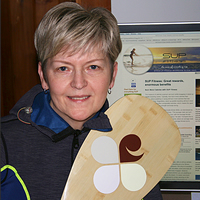 Kathy Verigin has short blonde hair and is holding a paddle. Behind her is a screen showing her new webpage.
