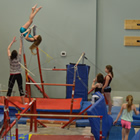 Group of girls performing gymnastics with coach