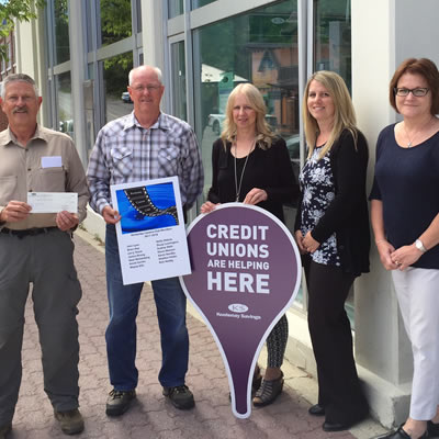 Kootenay Savings Kimberley Branch employees Dawn Marchi, Leanne Perrault and Susan Cleverly present Neal Weisenberg and John Lyon of the Kimberley Camera Club with a $750 cheque to help the Club purchase new equipment.