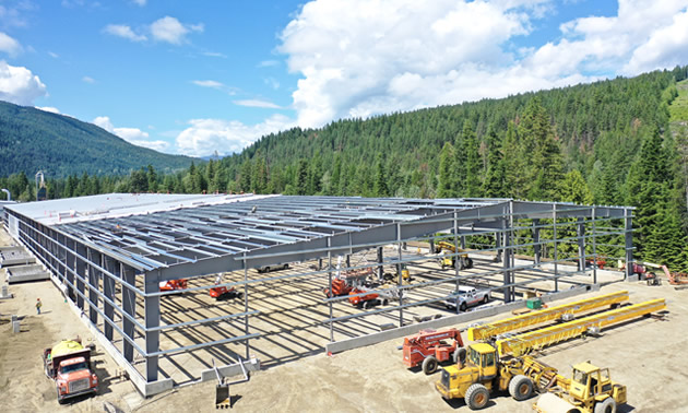 The partially built mass timber facility is shown, with the metal framework in place.